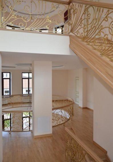 Большая деревянная лестница с кованным ограждением