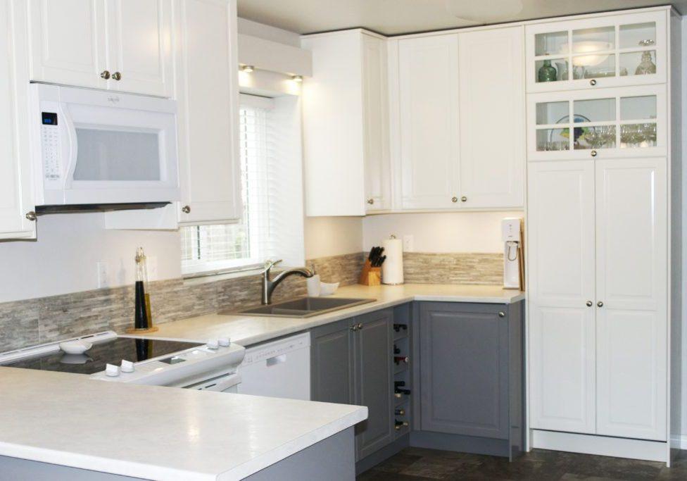 Белая п-образная кухня модерн под окно с барной стойкой