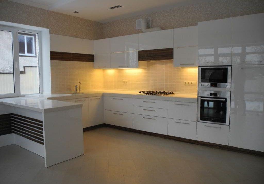 П-образная глянцевая белая кухня с деревом под окно, с барной стойкой