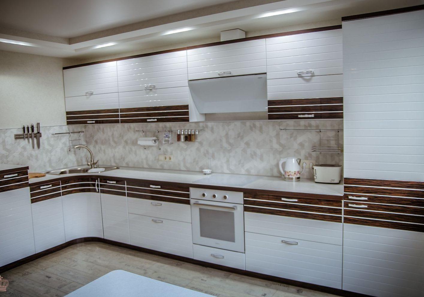 Угловая белая кухня в полоску с деревом, глянец