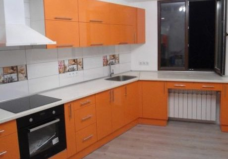 Угловая бело-оранжевая кухня под окно с барной стойкой глянец 2