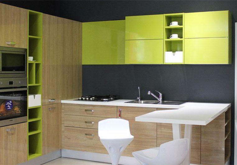 Угловая зеленая кухня с деревом и барной стойкой
