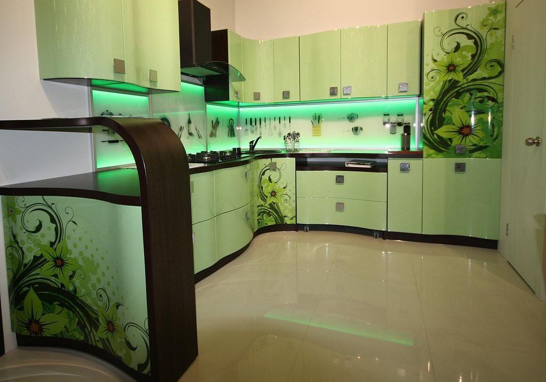 Угловая зеленая кухня с рисунком на фасаде и барной стойкой