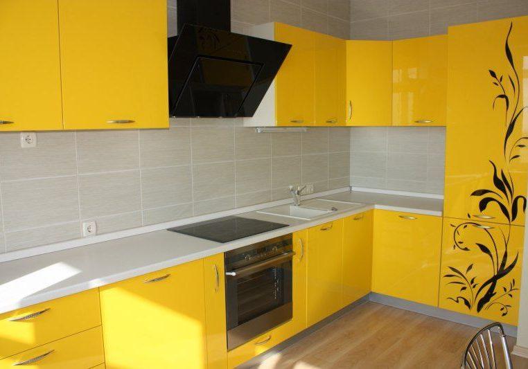 Желтая кухня углом с белой столешницей и черным рисунком на фасаде